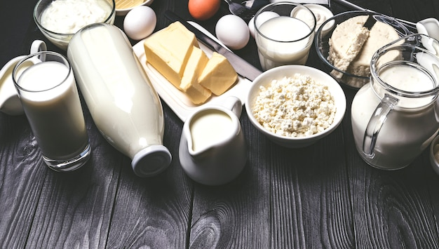 Different dairy products on black wooden table