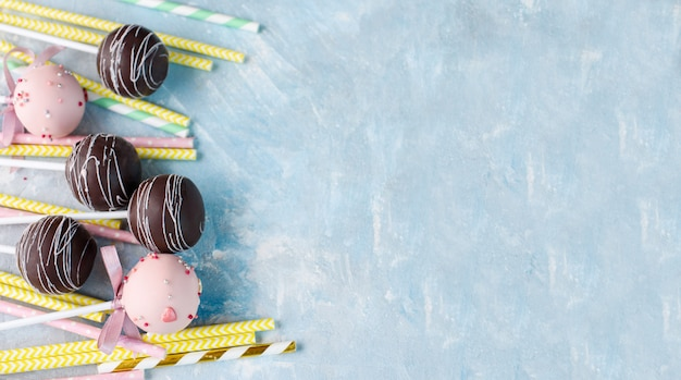 Different delicious cake pops with multi-colored drinking tubes on a blue concrete background.