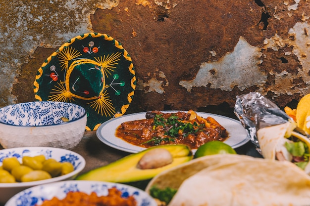 Different delicious mexican dishes over rusty background with mexican hat