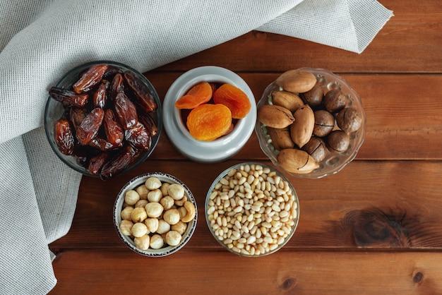 木製のテーブルにさまざまなおいしいナッツとドライフルーツ。上面図。健康食品とおやつ