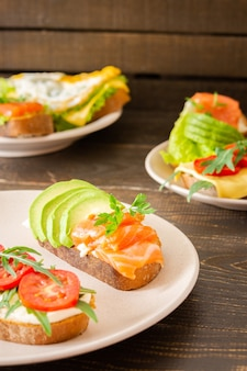 Different delicious sandwiches for breakfast, bread with cheese, avocado and trout, sandwich with egg, tomato and rucola, parsley