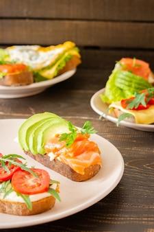 아침 식사로 다양한 맛있는 샌드위치, 치즈, 아보카도, 송어를 곁들인 빵, 계란, 토마토, 루콜라, 파슬리를 곁들인 샌드위치