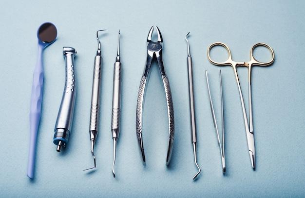 Различные стоматологические стальные инструменты на голубом фоне
