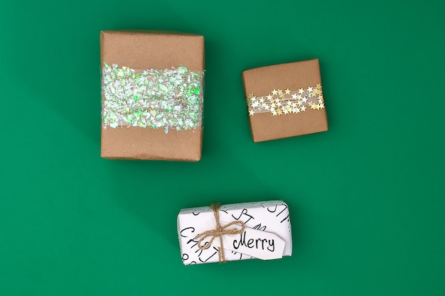 Different design of christmas gifts from craft paper on a green background.