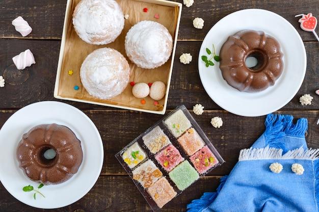 木製の表面にさまざまなデザート。チョコレートプリン、粉砂糖のマフィン、ターキッシュデライト。平面図、フラットレイアウト。