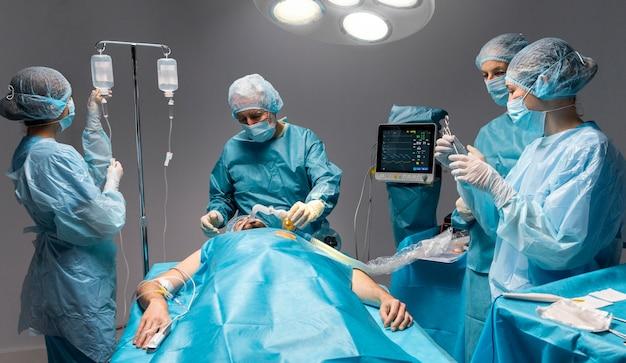 Разные врачи делают хирургическую процедуру пациенту