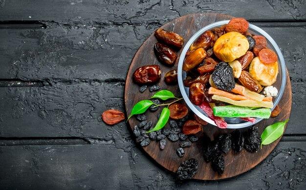 ボウルにさまざまなドライフルーツ。黒の素朴なテーブルの上。
