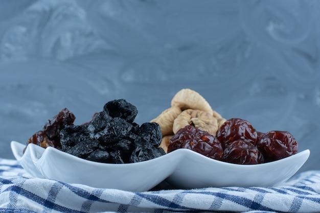 Diversi frutti secchi in una ciotola, sul canovaccio, sul tavolo di marmo.