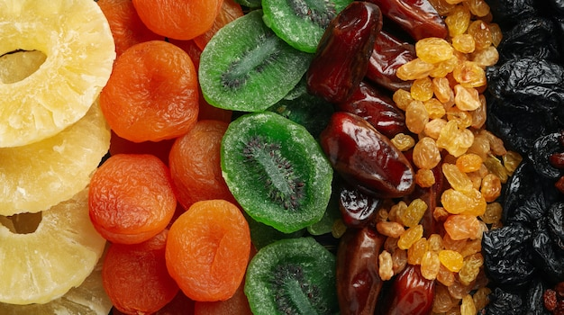 Different dried fruits and nuts on whole background