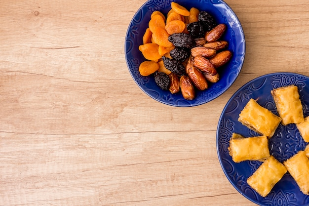 Different dried fruits with eastern sweets on plate