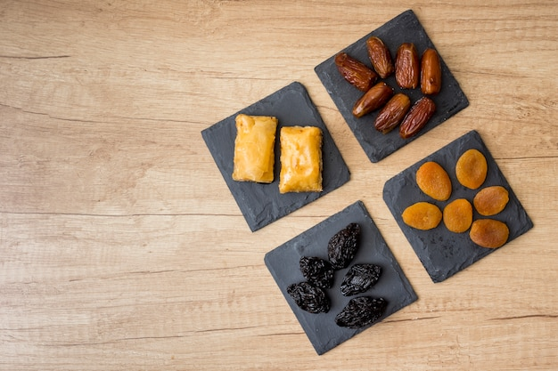 Different dried fruits with eastern sweets on table