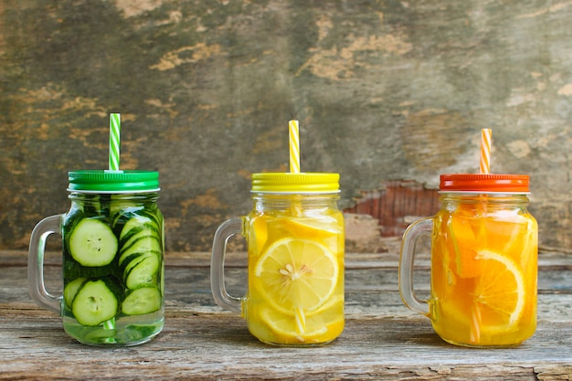 Different drinks of fruits and vegetables on old wooden background.