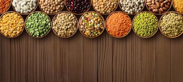 Различные сухие бобовые: горох, чечевица, фасоль, нут в деревянных мисках на деревянном столе. вид сверху.