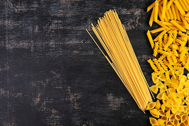 Different dry pasta on a wooden background. top view