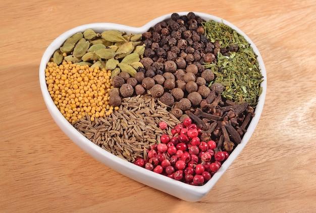 Различные сухие специи в тарелке в форме сердца