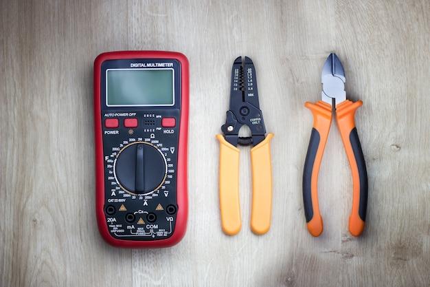 木製テーブルのさまざまな電動工具デジタルマルチメーターカッティングプライヤーとケーブルストリッパー