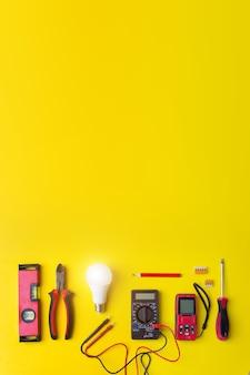 Различные электрические инструменты на желтом фоне с блеском. компоненты для использования в электроустановках.