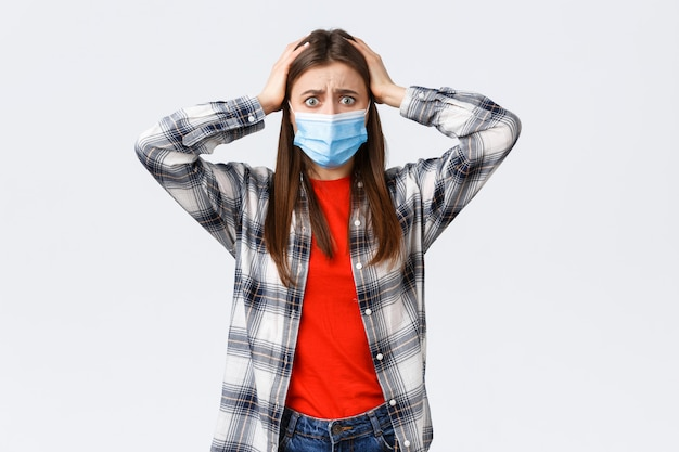 Different emotions, covid-19 pandemic, coronavirus self-quarantine and social distancing concept. alarmed and worried, panicking young woman in medical mask, grab head indecisive, feel scared