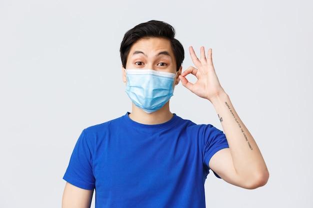 코로나바이러스, covid-19 개념 동안 다른 감정, 생활 방식, 여가. 문제 없다. 열정적인 젊은 아시아 남성이 제품이나 서비스를 추천하고 의료 마스크에 괜찮은 표시를 보여줍니다.