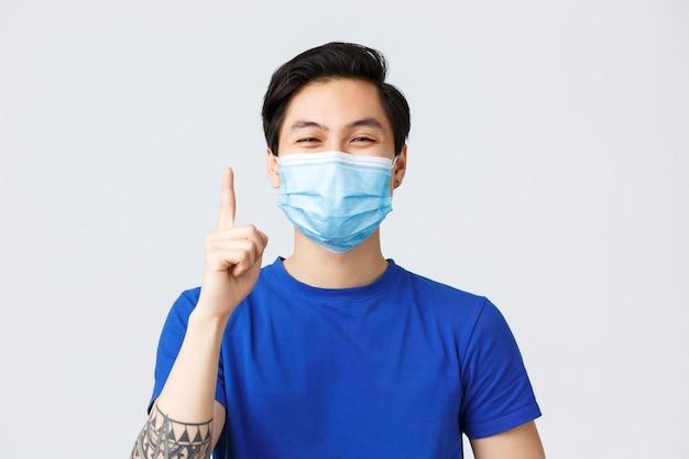 コロナウイルス中のさまざまな感情、ライフスタイル、レジャー、covid-19コンセプト。提案、メイクアップのアイデアや解決策を言うために人差し指を上げる医療マスクで幸せな若いアジア人男性のクローズアップ。