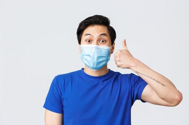 코로나바이러스, covid-19 개념 동안 다른 감정, 생활 방식, 여가. 의료용 마스크와 파란색 티셔츠를 입은 열정적인 행복한 아시아 남자는 지지와 승인을 보여주고 엄지손가락을 치켜들다