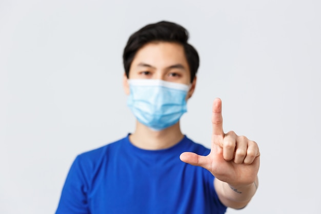 Different emotions, lifestyle and leisure during coronavirus, covid-19 concept. blurred shot of asian guy with focus on hand showing l word, wearing medical mask from virus, grey background