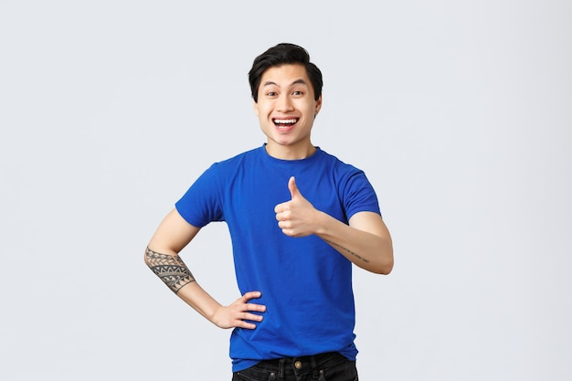 다른 감정, 사람들의 생활 방식 및 광고 개념. 파란색 티셔츠를 입은 열정적인 아시아 남성, 긍정적인 미소로 승인에 엄지손가락을 치켜들고 제품, 회색 배경을 좋아하고 추천합니다.