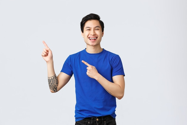 다른 감정, 사람들의 생활 방식 및 광고 개념. 파란색 티셔츠를 입은 근심 없는 아시아 남자, 왼쪽 위 모서리를 가리키며 기뻐하며 웃고 있는 멋진 새 프로모션 소개, 배너 표시