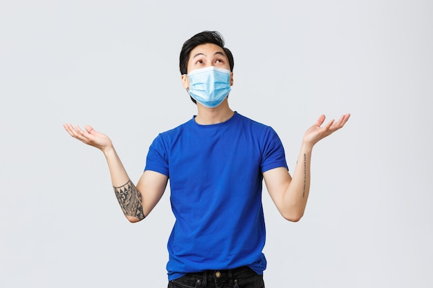 Different emotions, social distancing, self-quarantine on coronavirus and lifestyle concept. grateful and happy young asian man in medical mask, looking and raising hands up air as raining, falling
