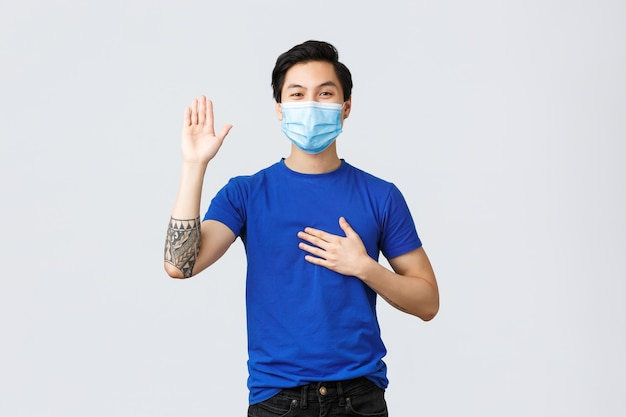Different emotions, social distancing, self-quarantine on covid-19 and lifestyle concept. honest happy smiling asian man making promise, hold hand on heart and arm raise while tell truth