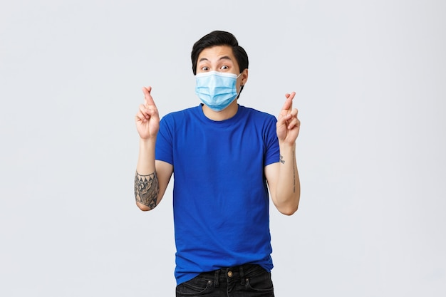 Different emotions, social distancing, self-quarantine on covid-19 and lifestyle concept. hopeful excited asian man anticipating good news, cross finger wear medical mask