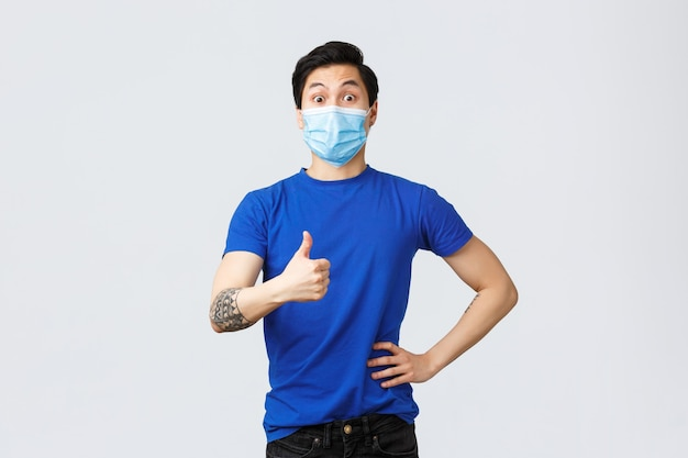 Different emotions, social distancing, self-quarantine on covid-19 and lifestyle concept. surprised and impressed supportive asian guy thumbs-up to good idea, wearing medical mask