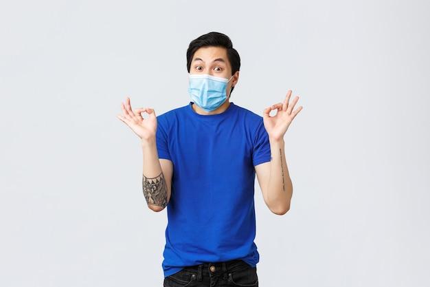 다른 감정, 사회적 거리, covid-19 및 생활 방식 개념에 대한 자가 격리. 의료용 마스크를 쓴 행복한 아시아 남자, 괜찮은 사인과 미소, 훌륭한 아이디어, 멋진 계획을 보여줍니다.