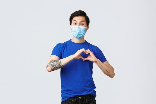 さまざまな感情、社会的距離、covid-19の自己検疫、ライフスタイルの概念。ケアや愛、同情を表現するために胸にハートのサインを示す医療マスクの魅力的なアジア人男性