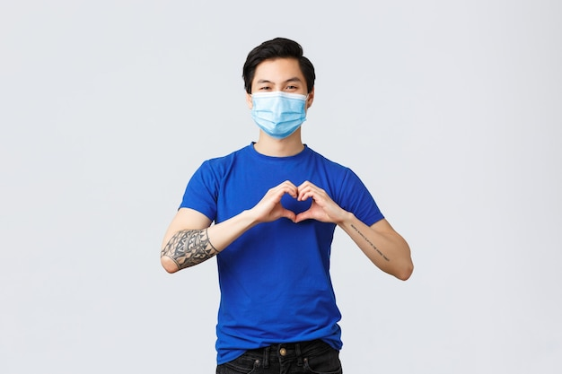 さまざまな感情、社会的距離、covid-19の自己検疫、ライフスタイルの概念。医療マスクとtシャツでハンサムなアジア人のボーイフレンドを気遣い、ハートのサインを示し、誰かを気遣い、愛します