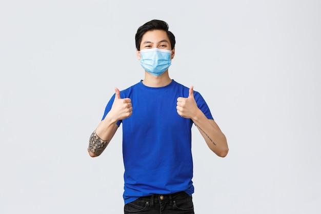 다른 감정, 사회적 거리, covid-19 및 생활 방식 개념에 대한 자가 격리. 의료용 마스크를 쓴 쾌활하고 지지적인 젊은 아시아 남성은 개인 보호 장비를 사용하도록 권장합니다.