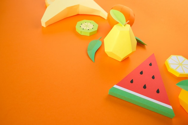 Different exotic fruits made of paper on orange background