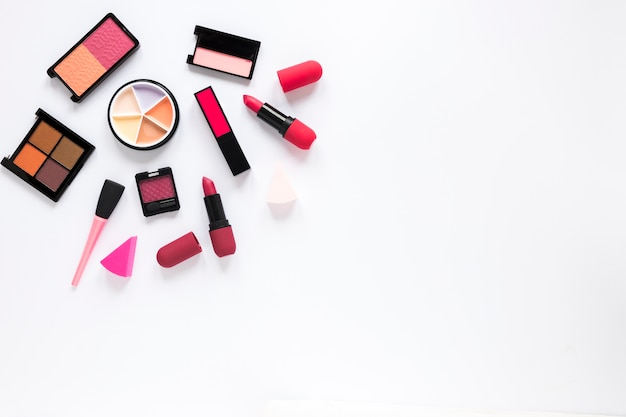 Different eye shadows with lipsticks on table