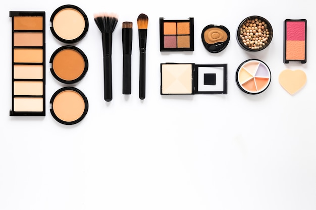 Different facial powders with powder brushes on white table