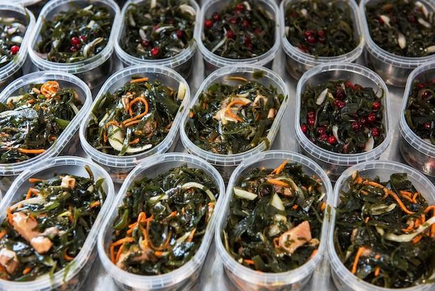 Различная рыба и салат из морских водорослей чука вакаме в пластиковых мисках. концепция производства здоровой пищи или доставки еды