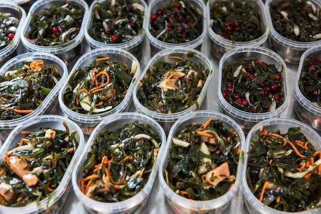 Different fish and chuka wakame laminaria seaweed salad in plastic bowles. concept of healthy food production or delivery food