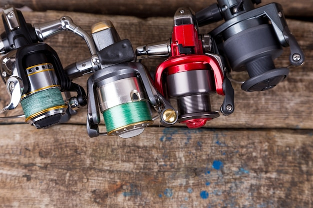 Different fishing reels with line on wooden table