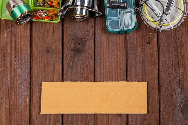 Различные рыболовные снасти с приманками и катушками на деревянном коричневом фоне с местом для текста. дизайн для рекламы и издательского дела.