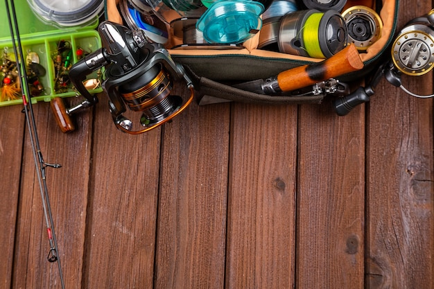 Different fishing tacles with lures and reels on wooden brown background with place for text. design for advertisment and publishing.