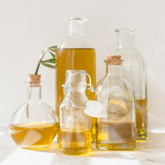 Different flasks and bottles of oil against white backdrop