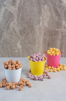 Different flavors and colors of popcorn candy assorted into colorful buckets on marble.