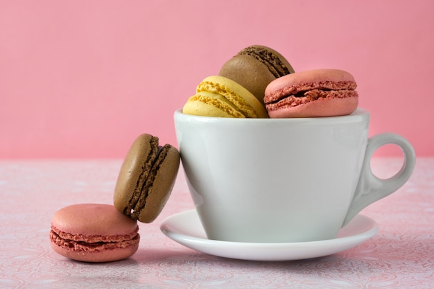 Different flavors of macarons on a mug