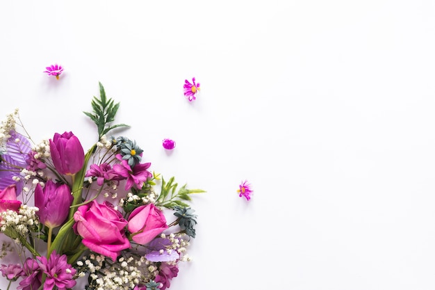 Different flowers scattered on white table