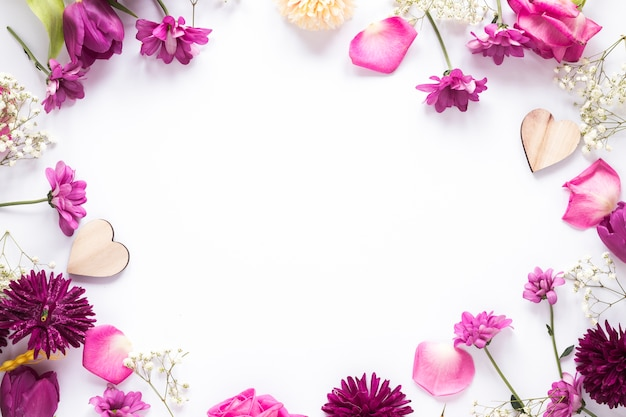 Different flowers with wooden hearts on table