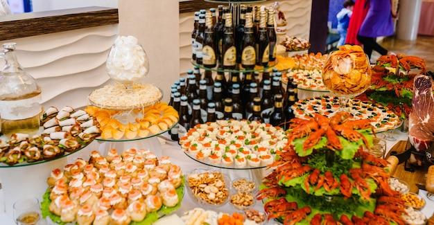 나무 테이블에 요리된 다른 음식 가재, 오징어, 해산물. 술과 음식. 테이블에 스낵과 함께 맥주입니다. 실내 음식 개념입니다.